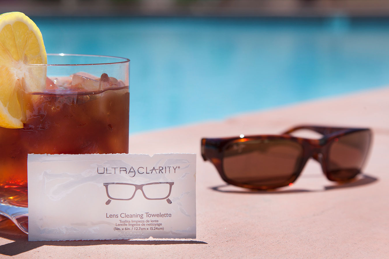Lens Cleaning towelette, drink & sunglasses by the pool at The Hacienda in Gay Palm Springs